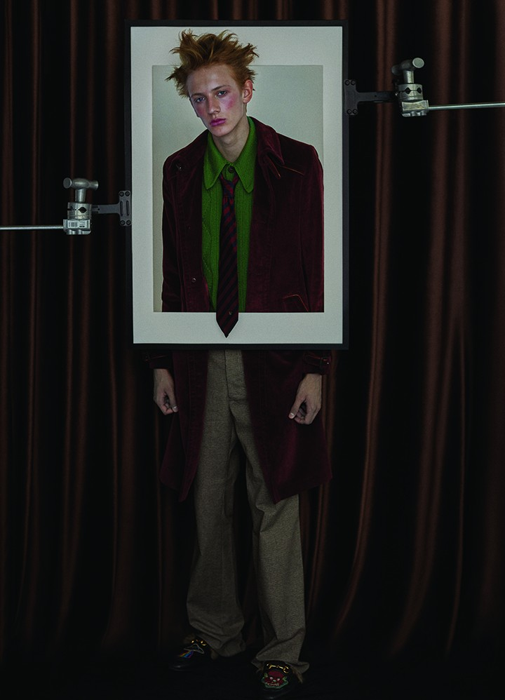 Prada 深红色灯芯绒风衣外套、绿色针织衫 Bottega Veneta 卡其色细格纹喇叭长裤  Gucci 黑色图案刺绣毛毛皮鞋 Stylist's Own 红色条纹领带